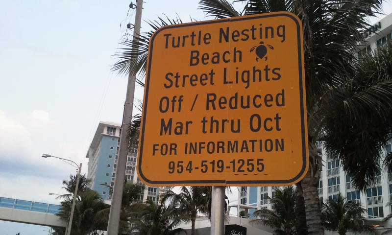 Sign explaining why street lights are dimmed.