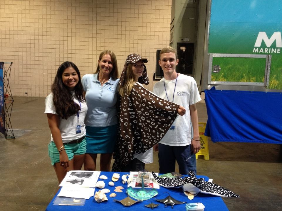 """(From left to right) Mote intern Bella Genta, Project PI Kim Bassos-Hull, Mote research intern Breanna DeGroot (aka """"Doty"""" the spotted eagle ray), and Mote intern Sean Russell show off cool things about rays at Shark Con in Tampa, FL. Photo credit: Kim Bassos-Hull – Mote Marine Lab"""