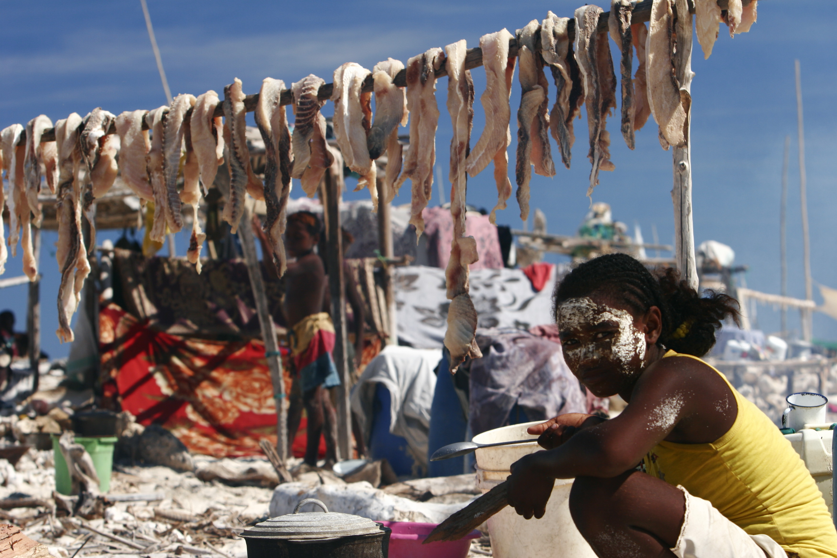 A woman prepares food in her temporary home on the Barren Isles. Shark meat is drying in the background. Photo © Garth Cripps